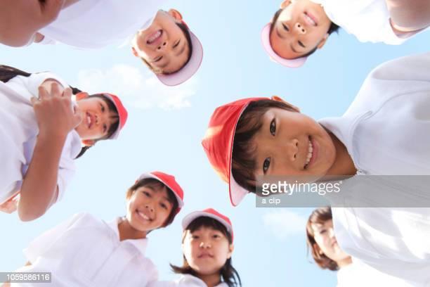 輪になってカメラを覗く体操服姿の小学生と先生 - 囲む ストックフォトと画像