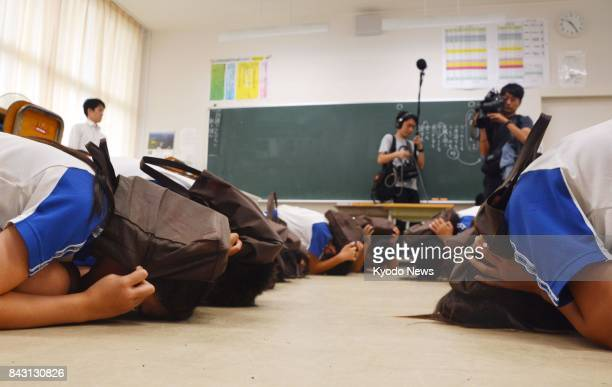 Elementary school students hold their heads and keep their bodies low during an emergency drill in the western Japan town of Okinoshima on Sept 6 in...