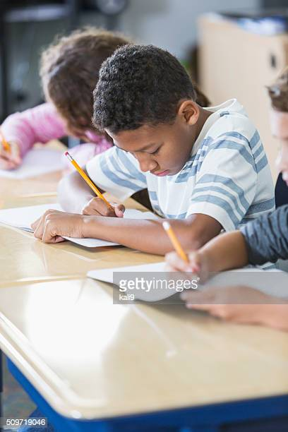 Elementary school students in class taking test