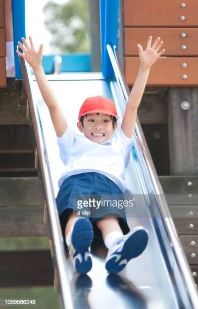 滑り台で遊ぶ体操服姿の小学生