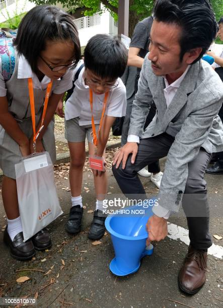 Elementary school students look at a SATO toilet system made by Japanese household products firm Lixil during a special interactive class with...