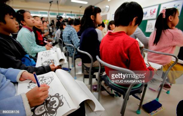 Elementary school students look at mascot choices for the Tokyo 2020 Olympics in Chofu Tokyo on December 11 2017 From December 11 to February 22...