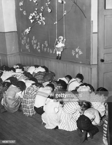 Elementary school students practicing a 'Duck and Cover' air raid drill Cleveland Ohio May 1951