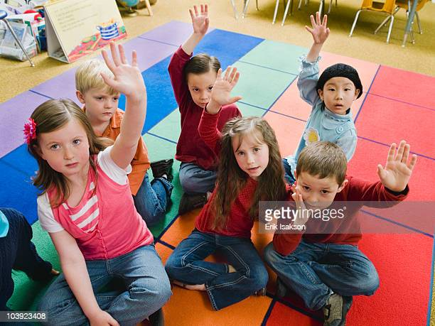 Elementary school students raising their hands