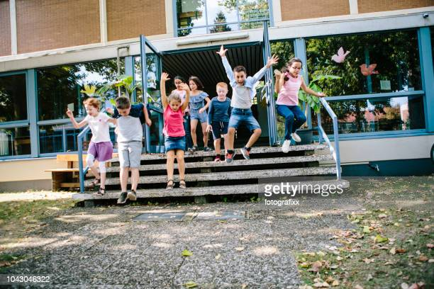 elementary school students run out of school to schoolyard - school building stock pictures, royalty-free photos & images