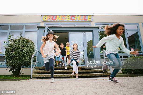 elementary school students run out of school to schoolyard - schulgebäude stock-fotos und bilder