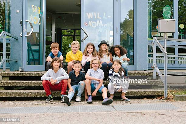 Elementary school students sit in front of school building