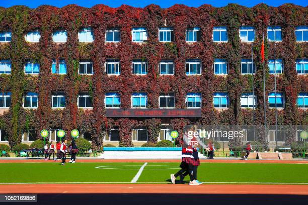 Elementary school students walk past a playground in front of a school building covered by leaves of the Virginia creeper in Shenyang in China's...