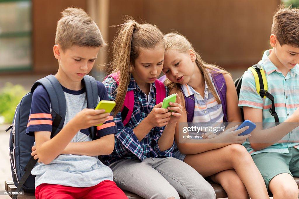 elementary school students with smartphones : Stock-Foto