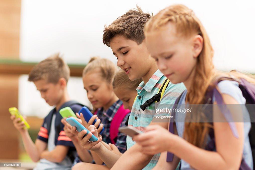 elementary school students with smartphones : Stock Photo