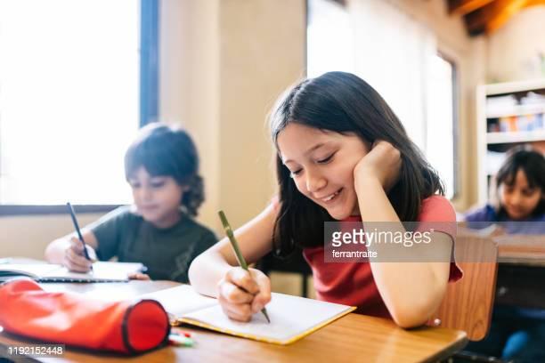 alumnos de la escuela primaria escribiendo en cuaderno - 8 9 años fotografías e imágenes de stock