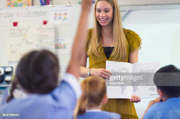 elementary school  teacher giving a presentation to the class. - teacher stock pictures, royalty-free photos & images