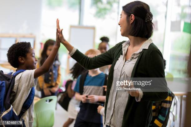 elementary school teacher high fives student - teacher stock pictures, royalty-free photos & images