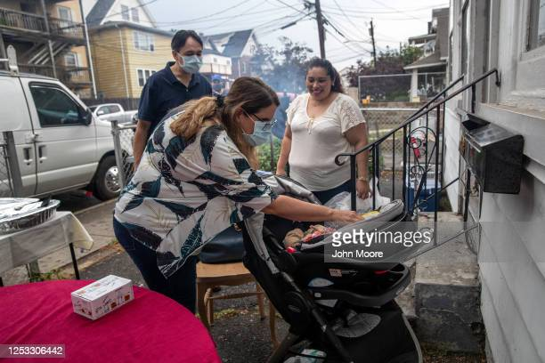 Elementary school teacher Luciana Lira greets baby Neysel, 10 weeks, at a dinner celebrating his three month birthday on June 28, 2020 in Stamford,...