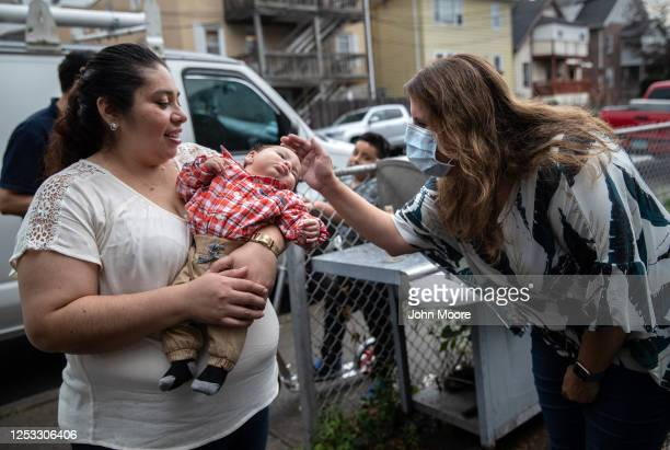 Elementary school teacher Luciana Lira speaks with baby Neysel 10 weeks and his mother Zully at a dinner celebrating Neysel's three month birthday on...
