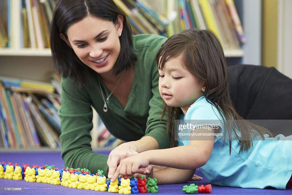 Elementary school teacher practicing counting with a student : Stock Photo