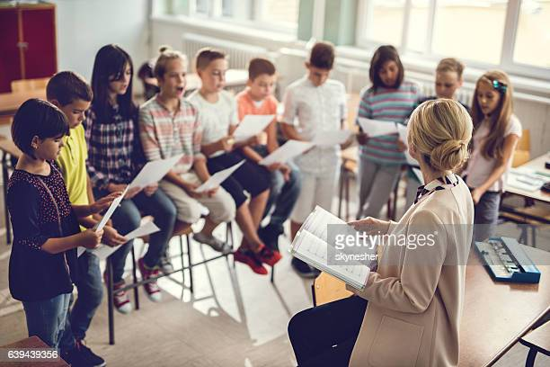 Elementary school teacher singing with children in the classroom.