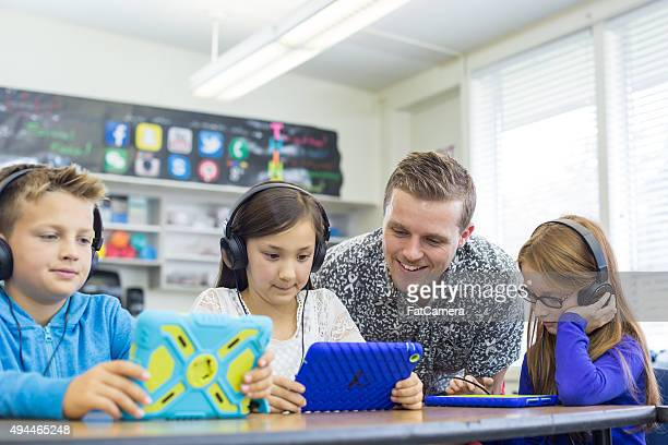 Elementary school teacher works with students on digital