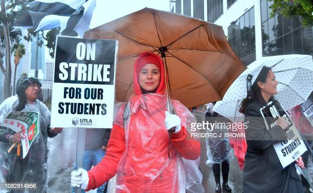 Elementary school teacher Yevgeniya Pokhilko holds her 'On Strike' sign joining thousands of teachers who marched in the rain through Los Angeles...