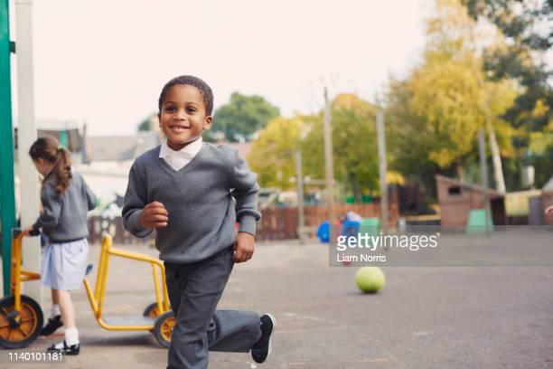 elementary schoolboy and girl running in school playground - britain playgrounds stock pictures, royalty-free photos & images