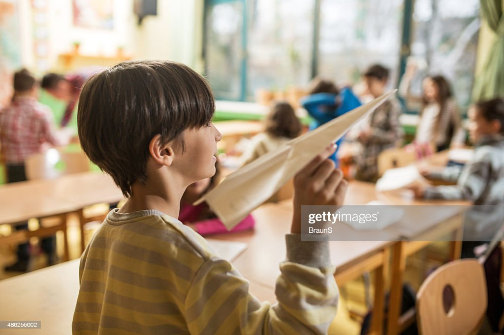 Elementary schoolboy ready to throw paper airplane in the classroom. : Stock Photo