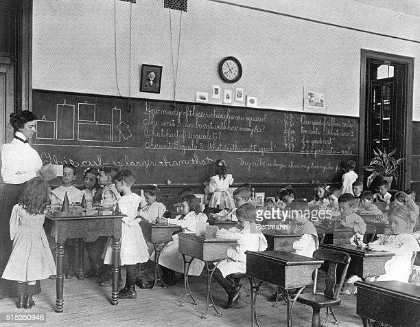 Elementary schoolchildren sit at their desk, while others stand around their teacher, during a lesson on shapes.