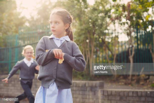elementary schoolgirl eating cracker in playground - hongerig stockfoto's en -beelden