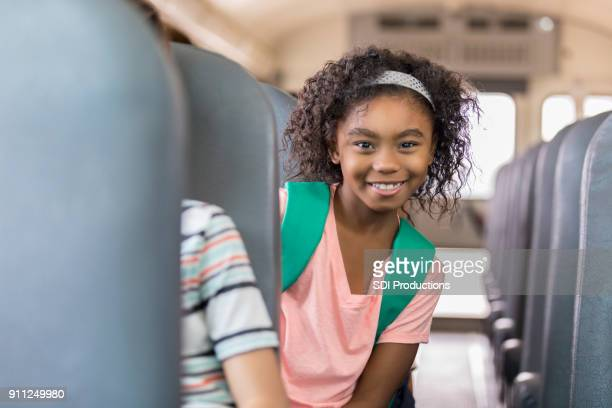 elementare schulmädchen reitet den schulbus - staatliche schule stock-fotos und bilder