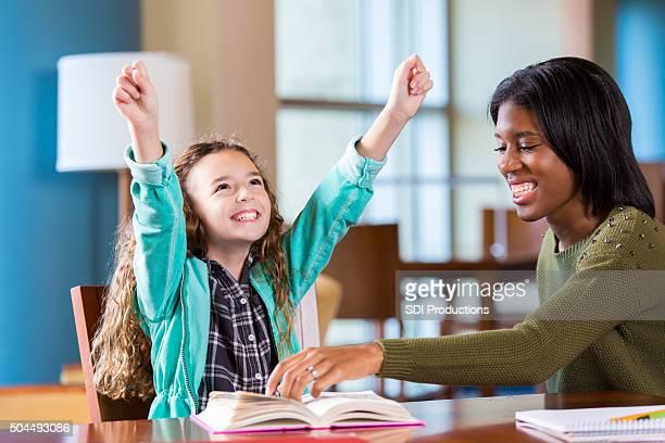 Elementary student Hausaufgaben während feiert Erfolg mit tutor