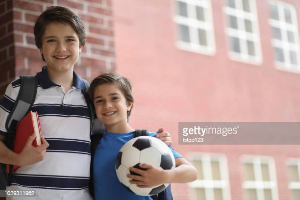 elementary student friends, brothers on campus. - sibling stock pictures, royalty-free photos & images