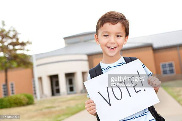 Elementary student holding a Vote sign in front of school