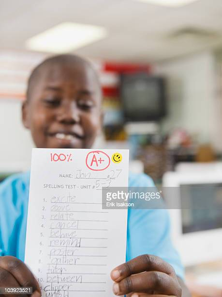 Elementary student holding an A grade paper