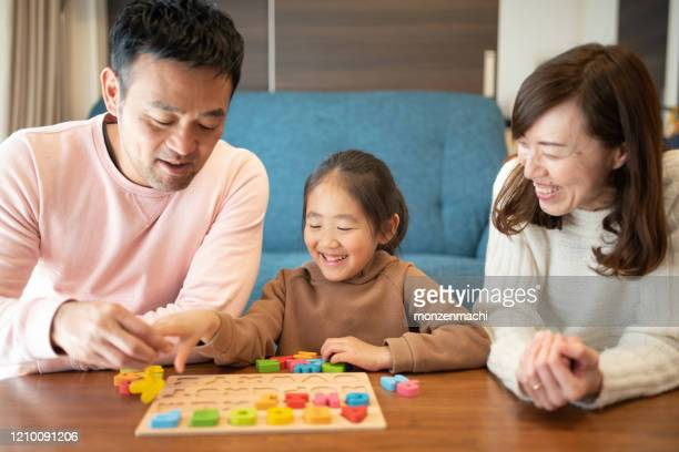 elementary student learning english with parents at home - english language stock pictures, royalty-free photos & images