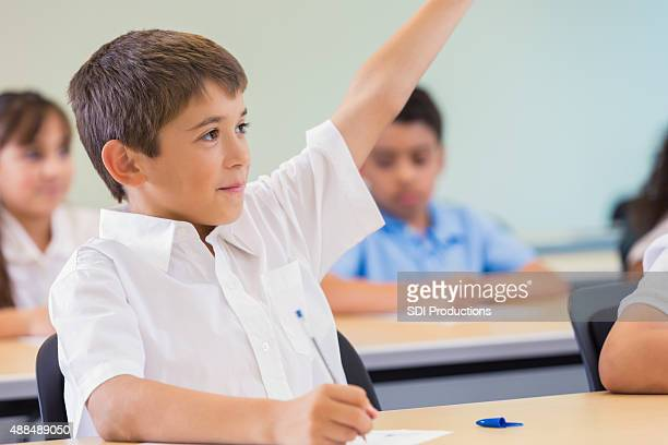 Elementary student raising hand to answer question in class