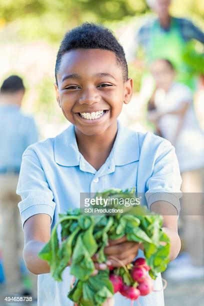 Elementary student smiling, holding vegetables in school garden