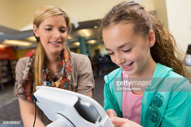 Grundschüler mit Digitaltablett in der öffentlichen Bibliothek