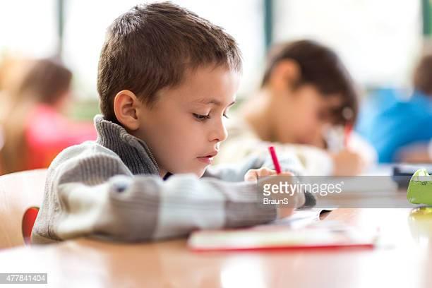 Escuela primaria escribiendo en una computadora portátil en una clase.