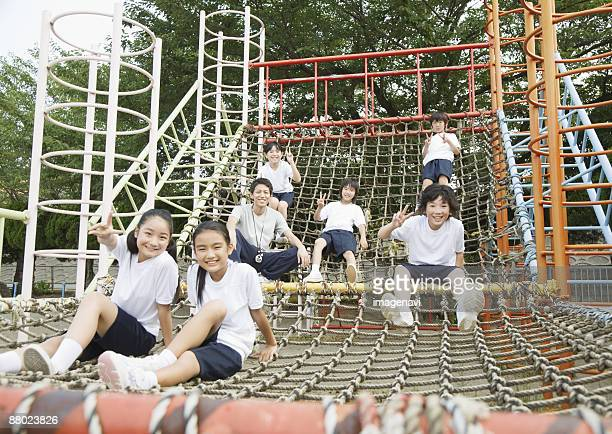 Elementary students and teacher sitting on play equipment