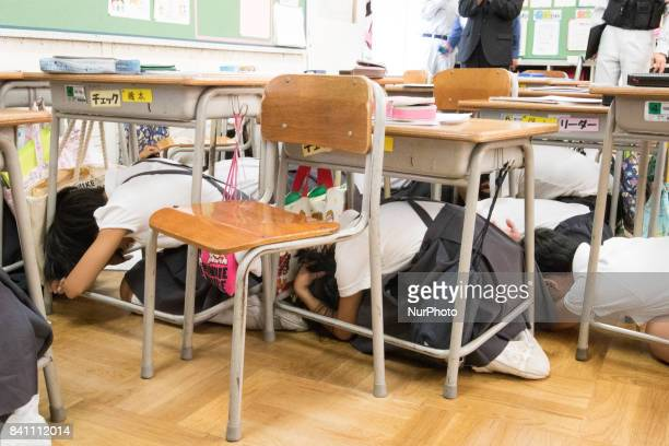 Elementary students cover under their desks during an evacuation drill in preparation for a North Korea'n ballistic missile attack that might happen...