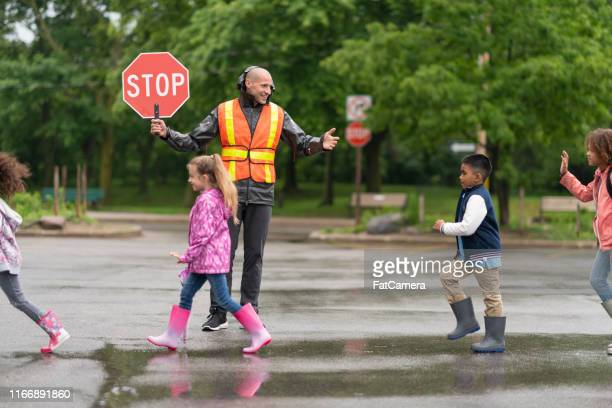 elementary students cross street with help from crossing guard - transportation occupation stock pictures, royalty-free photos & images