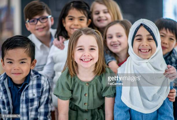 elementary students grouped together smiling - headscarf stock pictures, royalty-free photos & images
