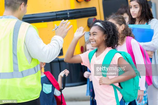 elementary students high five school bus driver - state school stock pictures, royalty-free photos & images