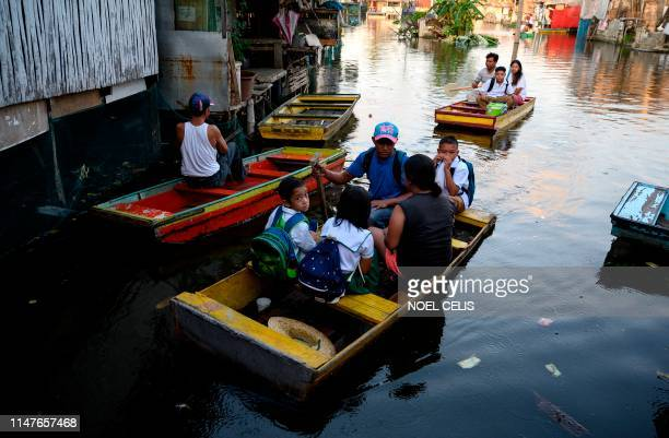 TOPSHOT Elementary students living on flooded Artex Compound ride on makeshift boat to attend the first day of school in Panghulo 1 Elementary School...