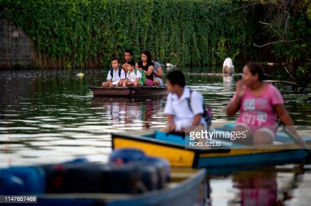 Elementary students living on flooded Artex Compound ride on makeshift boat to attend the first day of school in Panghulo 1 Elementary School in...