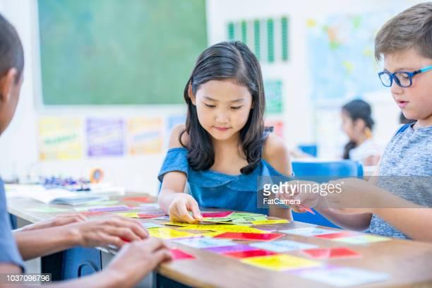 alunos do ensino fundamental jogam conceituais em suas mesas - carta de baralho jogo de lazer - fotografias e filmes do acervo