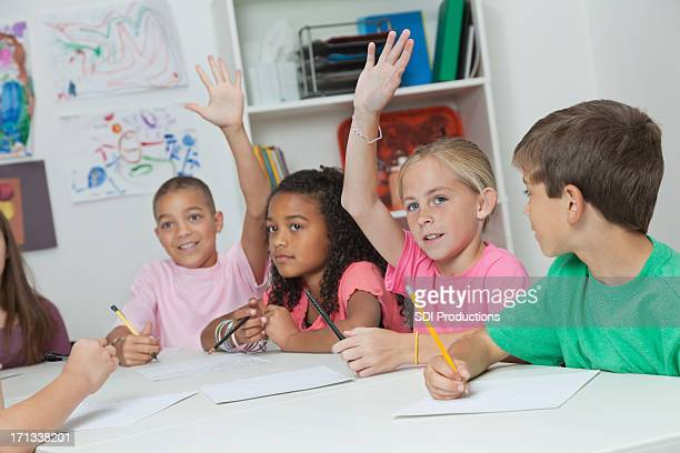 Elementary students raising hands in class