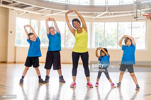 Elementary Students Stretching During Gym Class
