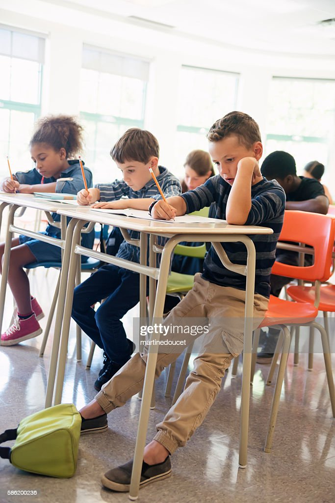 Elementary students taking a test in classroom. : Stock Photo