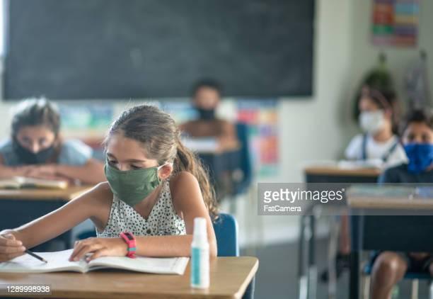 grundschüler tragen masken im klassenzimmer - staatliche schule stock-fotos und bilder