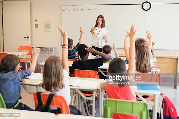 Elementary students with hand raised in class with teacher.